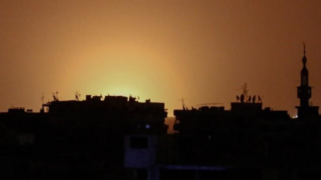 صورة تم إلتقاطها من بلدة دوما التي  يسيطر عليها المتمردون تظهر ألسنة النار عن بُعد والتي يُعتقد أنها تعلو من مطار دمشق الدولي التي تبعت انفجارا هز المنطقة في صباح 27 أبريل، 2017. (AFP PHOTO / Sameer Al-Doumy)
