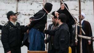 بلال عبد الله، الذي قتل الشاب علد الله حسين زاده خلال شجار في الشارع بسكين في عام 2007، يُنقذ من حبل المنشقة من قبل والدة ضحيته خلال عملية إعدام في مدينة نوشهر شمال إيران، 15 أبريل، 2014. (AFP/Arash Khamooshi/ISNA)