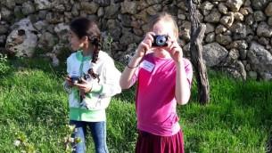 """فتاتان إسرائيلية وفلسطينية تلتقطان الصورة مع في """"أرض""""، في إطار مبادرة """"جذور"""" للعيش المشترك. (Brett Kline/Times of Israel)"""