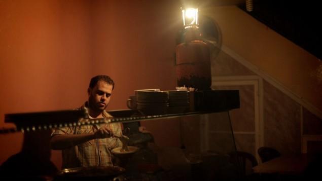 فلسطيني يستخدم قنديل غاز خلال عمله داخل مطعم أثناء انقاطع للكهرباء في قطاع غزة، 17 نوفمبر، 2013. (Emad Nassar/Flash90)