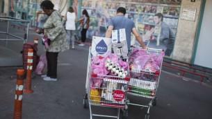 صورة توضيحية لإسرائيليين امام متجر في حي تلبيوت في القدس، 20 ابريل 2016 (Hadas Parush/Flash90)
