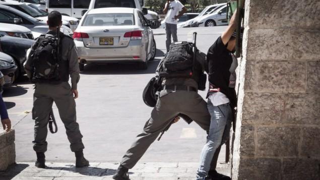 عنصر من شرطة حرس الحدود الإسرائيلية يقوم بتفتيش شاب فلسطيني عند باب العامود في البلدة القديمة في القدس، 20 سبتمبر، 2016. (Sebi Berens/Flash90)