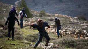 صورة للتوضيح: متظاهرون شبان يهود يلقون الحجارة على قوات الشرطة في بؤرة عامونا الإستيطانية غير القانونية، 1 فبراير، 2017، في صباح إخلاء المستوطنة. (Hadas Parush/Flash90)
