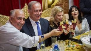 رئيس الوزراء بينيامين نتنياهو وزوجته سارة يحضران احتفالات 'الميمونة' التقليدية التي يحييها اليهود من أصول مغربية، في مدينة الخضيرة، 17 أبريل، 2017.(Ido Erez/POOL)