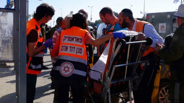 مسعفون يقدمون العلاج لرجل أصيب بجروح طفيفة في هجوم دهس وقع في مفرق غوش عتصيون في الضفة الغربية، 19 أبريل، 2017. (Magen David Adom)