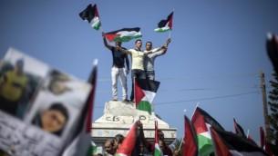 فلسطينيون في غزة يلوحون  بأعلام فلسطينية خلال تظاهرة دعما للوحدة الوطنية في 22 أكتوبر، 2016 في مدينة غزة. (AFP PHOTO / MAHMUD HAMS)