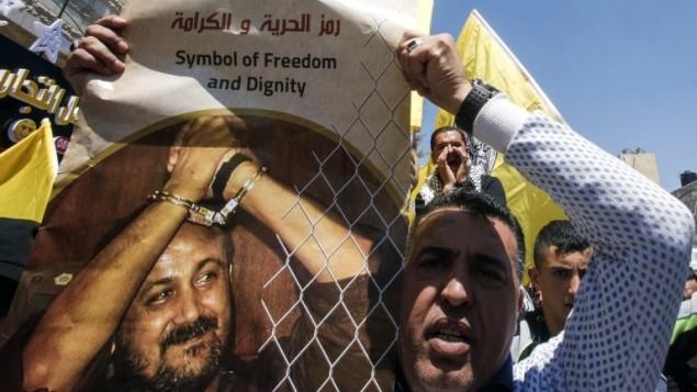 رجل يحمل صورة للقيادي والأسير الفلسطيني مروان البرغوثي يدعو إلى إطلاق سراحه خلال تظاهرة تضامن مع الأسرى في السجون الإسرائيلية بعد أن أعلن المئات منهم عن إضرابهم عن الطعام، في مدينة الخليل في الضفة الغربية، 17 أبريل، 2017. (AFP Photo/Hazem Bader)