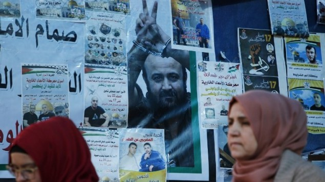 نساء فلسطينيان امام ملصق عليه صورة الاسير الفلسطيني المضرب عن الطعام مروان البرغوثي في رام الله، 24 ابريل 2017 (AFP/Abbas Momani)
