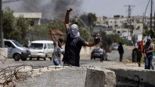 مواجهات بين فلسطينيين وجنود إسرائيليين خلال تظاهرة للتضامن مع الأسرى الفلسطينيين المضربين عن الطعام في السجون الإسرائيلية في بلدة سلواد بالضفة الغربية، 28 أبريل، 2017. (AFP Photo/Abbas Momani)