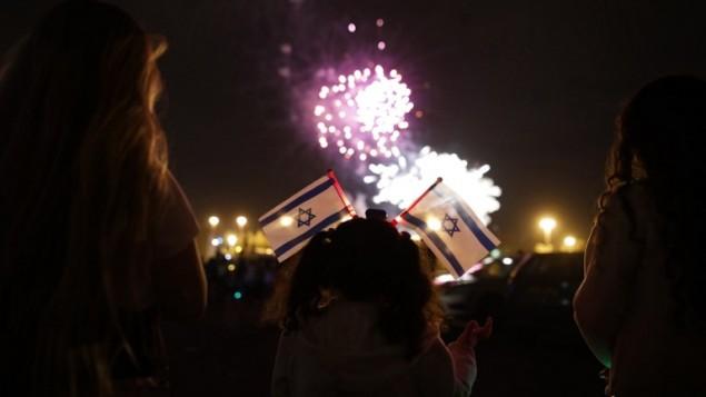 إسرائيليون يشاهدون عرض الألعاب النارية فوق 'جبل هرتسل' في القدس في نهاية 'يوم الذكرى' وبداية الإحتفالات ب'يوم الإستقلال ال69' لدولة إسرائيل، في القدس، 1 مايو، 2017. (AFP PHOTO / MENAHEM KAHANA)