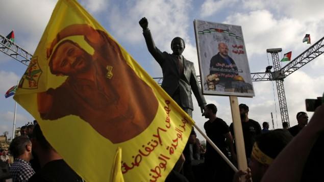 متظاهرون يحملونم صورا لمروان البرغوثي أمام تمثال نيلسون مانديلا في مدينة رام الله في الضفة الغربية، 3 مايو، 2017، خلال تظاهرة تضامن مع الأسرى الفلسطينيين في السجون الإسرائيلية. (AFP/ABBAS MOMANI)
