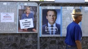 رجل يمر من أمام ملصقات إنتخابية بالقرب من محطة إقتراع في سان لو، 7 مايو، 2017، خلال الجولة الثانية من الإنتخابات الرئاسية الفرنسية.  (AFP PHOTO / Richard BOUHET)