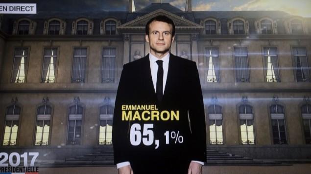 صورة لشاشة تلفزيون تظهر الرئيس الفرنسي المنتخب ايمانويل ماكرون مع نتيجة الانتخابات المقدرة، 7 مايو 2017 (AFP/OLIVIER MORIN)