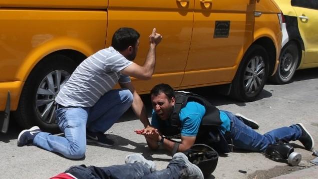 صحفي فلسطيني مصاب بجانب جثمان رجل قال مسؤولون فلسطينيون انه قُتل على يد مستوطن اسرائيلي خلال اشتباكات بالقرب من حاجز حوارة في الضفة الغربية، 18 مايو 2017 (AFP PHOTO / JAAFAR ASHTIYEH)