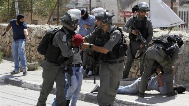 عناصر حرس الحدود والشرطة السرية يعتقلون متظاهرين فلسطينيين خلال اشتباكات عند مدخل مدينة بيت لحم في الضفة الغربية، 19 مايو 2017 (AFP PHOTO / Musa AL SHAER)