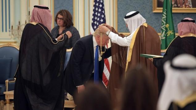 الرئيس الأمريكي دونالد ترامب (الوسط) يحصل على وسام الملك عبد العزيز آل سعود من الملك السعودي سلمان بن عبد العزيز آل سعود (من اليمين) في الديوان الملكي في الرياض، 20 مايو، 2017. (AFP PHOTO / MANDEL NGAN)