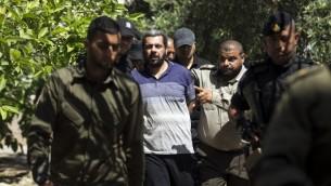 قوات امن حماس تقتاد هشام العلول، الرجل البالغ 44 عاما المتهم باغتيال القيادي في حركة حماس مازن فقهاء، بعد محكمته في محكمة عسكرية في فزة، 21 مايو 2017 (AFP/Mahmud Hams)
