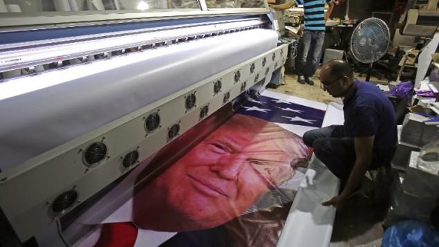 فلسطينيون يطبعون لافتة عليها صورة الرئيس الامريكي دونالد ترامب في بيت لحم، 21 مايو 2017 (AFP PHOTO / Musa AL SHAER)