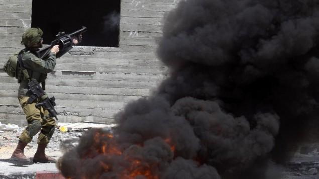 جندي اسرائيلي يطلق قنابل غاز باتجاه متظاهرين فلسطينيين خلال اشتباكات في بلدة دير شرف في الضفة الغربية، غربي نابلس، 22 مايو 2017 (JAAFAR ASHTIYEH / AFP)