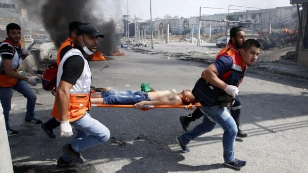 مسعفون فلسطينيون يقومون بإخلاء متظاهر مصاب خلال اشتباكات مع جنود اسرائيليين بعد مظاهرة دعم للاسرى الفلسطينيين المضربين عن الطعام في السجون الإسرائيلية وايضا لإدانة زيارة الرئيس الامريكي دونالد ترامب لإسرائيل والاراضي الفلسطينية في حاجز قلنديا، 22 مايو 2017 (ABBAS MOMANI / AFP)