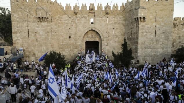 اسرائيليون يلوحون بالاعلام الإسرائيلية في باب العامود، خلال مسيرة احتفال بيوم القدس، في الذكرى الخمسين لتوحيد المدينة بعد حرب 1967، 24 مايو 2017 (AFP PHOTO / Menahem KAHANA)