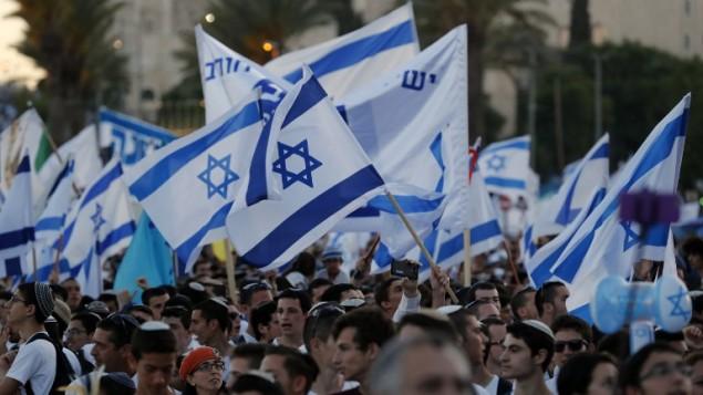 اسرائيليون يلوحون بالاعلام الإسرائيلية خلال مسيرة حول القدس القديمة، احتفال بيوم القدس، في الذكرى الخمسين لتوحيد المدينة بعد حرب 1967، 24 مايو 2017 (AFP PHOTO / Menahem KAHANA)