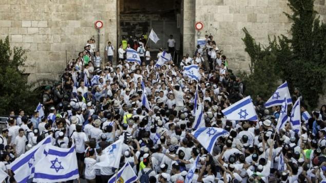 اسرائيليون يلوحون بالاعلام الإسرائيلية في باب العامود، خلال مسيرة احتفال بيوم القدس، في الذكرى الخمسين لتوحيد المدينة بعد حرب 1967، 24 مايو 2017 (AFP PHOTO / Thomas COEX)