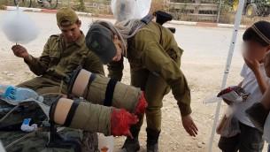 جنود من كتيبة عتصيون يعرضوا اقدام مصطنعة مقطوعة و'تنزف'، امام اطفال في مستوطنة تكوع ضمن عرض للجيش في يوم الاستقلال، 2 مايو 2017 (Courtesy)