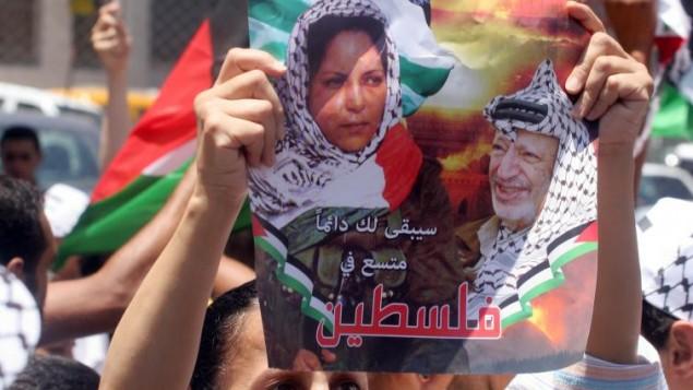 الفلسطينيون يحملون صورا لدلال المغربي، فلسطينية شاركت في عملية 'مجزرة الطريق الساحلي' في عام 1978 والتي أسفرت عن سقوط 38 إسرائيليا، في مدينة رام الله في الضفة الغربية، 16 يوليو، 2008. (Issam Rimawi/Flash90)