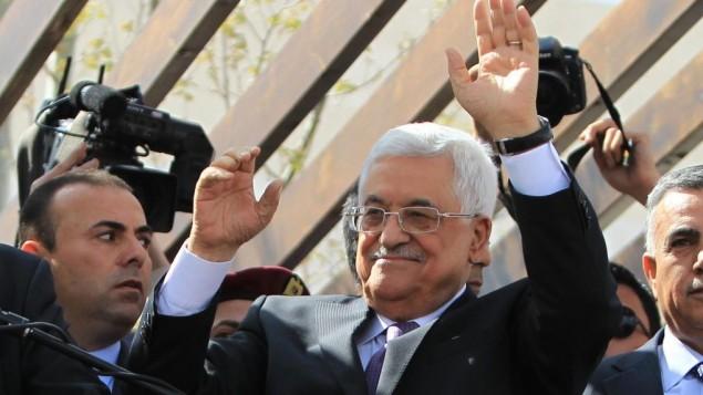 رئيس السلطة الفلسطينية محمود عباس يحيي مناصريه بعد رحلة إلى العاصمة الأمريكية واشنطن، 20 مارس، 2014، في مدينة رام الله بالضفة الغربية. (Issam Rimawi/Flash90)