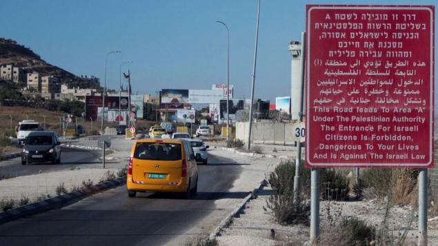 يافطة حمراء على جانب الطريق تحذر المواطنين الإسرائيليين من دخول مدينة نابلس في الضفة الغربية، 20 يوليو، 2015. (Garrett Mills/Flash90)