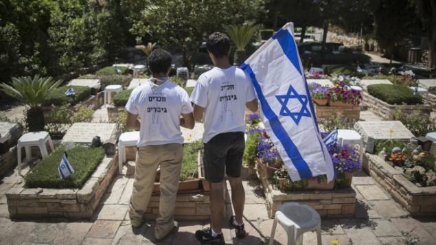 إسرائيليون يقفون أمام قبور جنود إسرائيليين قُتلوا خلال الحروبات  في المقبرة العسكرية في جبل هرتسل في القدس، 30 أبريل، 2017. (Yonatan Sindel/Flash90)
