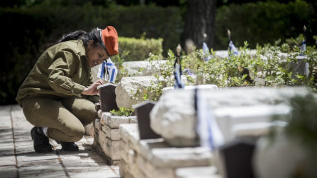 جنود إسرائيليون يضيئون الشموع عند قبور جنود قتلى في المقبرة العسكرية في جبل هرتسل في القدس، 30 أبريل، 2017. (Yonatan Sindel/Flash90)
