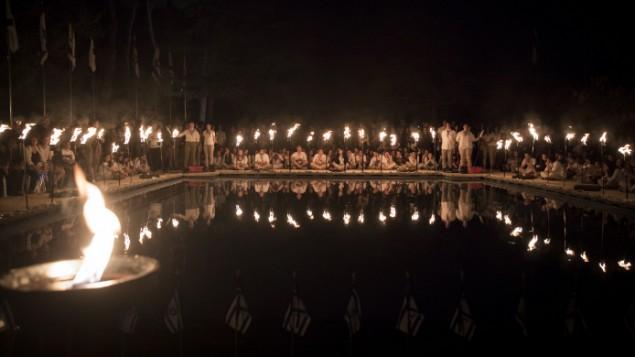 أعضاء سرية موديعين في الكشاف يضيئون المشاعل خلال مراسم لإحياء ذكرى الجنود ضحايا الحروبات، عشية 'يوم الذكرى' في المقبرة العسكرية في جبل هرتسل في القدس، 30 أبريل، 2017. (Yonatan Sindel/Flash90)