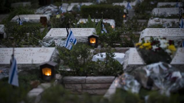 شموع مضاءة بالقرب من قبور الجنود القتلى  في المقبرة العسكرية في جبل هرتسل في القدس، 30 أبريل، 2017. (Yonatan Sindel/Flash90)