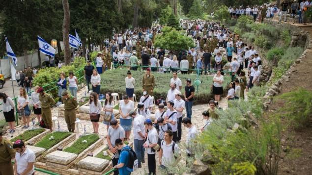 إسرائيليون يقفون لحظة صمت إلى جانب قبور جنود في المقبرة العسكرية في جبل هرتسل في القدس، مع إعلان صفارات الإنذار عن دقيقتي صمت في جميع أنحاء البلاد، لإحياء يوم ذكرى الجنود القتلى وضحايا الهجمات، 1 مايو، 2017.  (Yonatan Sindel/Flash90)