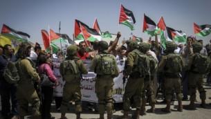 جنود إسرائيليون يوقفون تظاهرة لفلسطينيين عند حاجز حوارة، في مدينة نابلس في الضفة الغربية، 11 مايو، 2017.(Nasser Ishtayeh/Flash90)