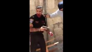 لقطة شاشة تظهر شرطيا بعد تعرضه للطعن من قبل منفذ هجوم السبت، 13 مايو، 2017 في البادة القديمة في القدس. الشرطة الإسرائيلية قالت إن المهاجم، مواطن أردني، قُتل بعد إطلاق النار عليه متأثرا بجروحه. وتم نقل الشرطي إلى المستشفى  في حالة متوسطة.  (screen capture: Quds News Network/Twitter)