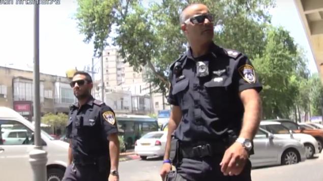 رجلا شرطة إسرائيليان مجهزان بكاميرات مثبتة على ثيابهم في إطار برنامج تجريبي للشرطة. (لقطة شاشة:YouTube)
