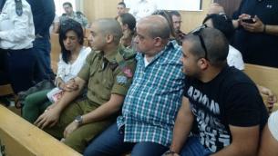 الجندي الإسرائيلي إيلور عزاريا يجلس بين والديه في قاعة المحكمة في مقر الجيش الإسرائيلي في تل أبيب خلال جلسة إستئناف الأربعاء، 3 مايو، 2017. (Judah Ari Gross/Times of Israel)