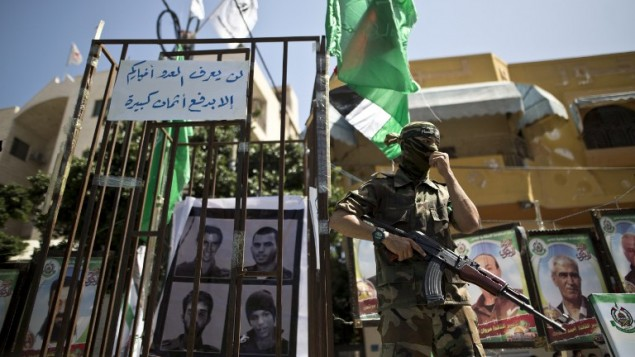 احد عناصر كتائب عز الدين القسام، الجناح العسكري لحركة حماس، بجانب زنزانة خلال مسيرة بمنسابة يوم الاسير في مدينة غزة، 17 ابريل 2016 (AFP Photo/Mahmud Hams)