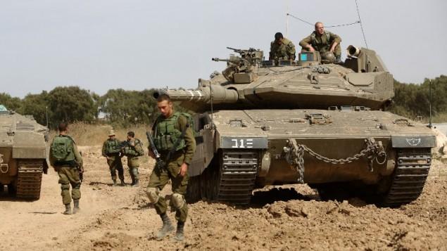 جنود إسرائيليون ودبابتهم يقومون بالحراسة على الحدود بين إسرائيل وقطاع غزة بالقرل من كبيوتس ناحال عوز جنوبي إسرائيل، 4 مايو، 2016. (AFP/Menahem Kahana)
