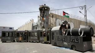 فلسطينيون يقفون على مجسم قطار في 15 مايو، 2016 أمام الجدار الفاصل الإسرائيلي خلال تظاهرة لإحياء ذكرى 'النكبة'. (AFP PHOTO / HAZEM BADER)