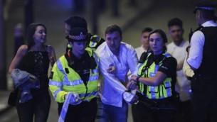 الشرطة ترافق مواطنا خلال إخلاء موقع هجوم وقع على جسر 'لندن بريدج' وسط لندن في 3 يونيو، 2017. (AFP PHOTO / DANIEL SORABJI)