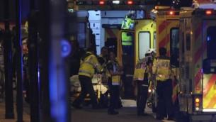رجال الشرطة وطواقم الإسعاف يقدمون العلاج لشخص مصاب في إعتداء وقع على جسر 'لندن بريدج' وسط لندن، 3 يونيو، 2017. (AFP PHOTO / DANIEL SORABJI)