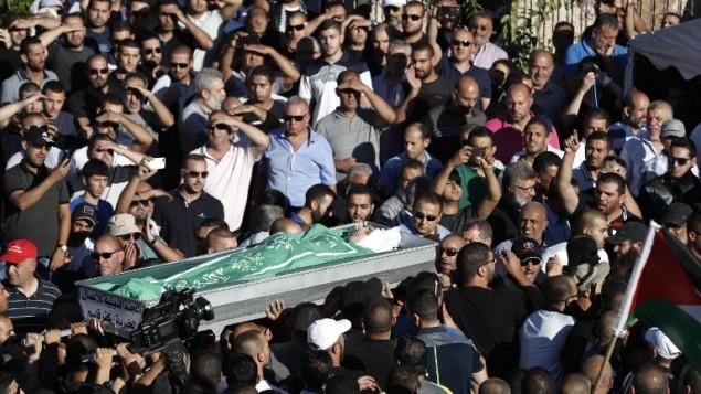 المشيعون يحملون جثمان محمد طه، الذي قُتل خلال مواجهات عندما حاول متظاهرون إقتحام محطة للشرطة فجرا، خلال جنازته في مدينة كفر قاسم العربية في وسط إسرائيل، 6 يونيو، 2017. (AFP/Ahmad GHARABLI)