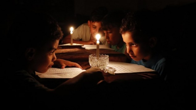أطفال فلسطينيون في منازلهم يقرؤون الكتب على ضوء الشموع بسبب نقص الكهرباء في مدينة غزة، 13 يونيو / حزيران 2017. (AFP/THOMAS COEX)