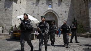 عناصر من شرطة حرس الحدود الإسرائيلية يسيرون خارج باب العامود في البلدة القديمة في مدينة القدس، 18 يونيو، 2017. (AFP/AHMAD GHARABLI)