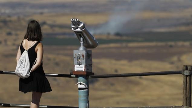 سائحة إسرائيلية تنظر إلى الجانب السوري من الحدود من جبل بنطل، في هضبة الجولان، 25 يونيو، 2017. (AFP Photo/Jalaa Marey)