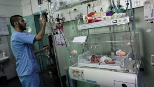 صورة توضيحية لممرض فلسطيني مع  حديث الولادة في وحدة العناية المركزة لحديثي الولادة في مستشفى الإمارات في رفح بجنوب قطاع غزة في 27 يونيو / حزيران 2017. (SAID KHATIB / AFP)
